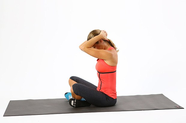 Photo of a woman completing the seated clasping neck stretch